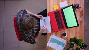 研究有绿色屏幕的膝上型计算机和分析图表与的年轻白种人商人特写镜头顶面射击  股票视频
