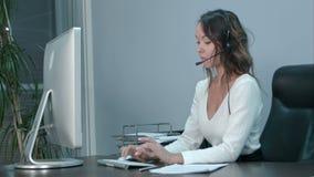 研究有耳机的膝上型计算机的友好的年轻亚裔女性操作员在现代办公室 股票视频