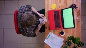 研究有采取笔记和喝的绿色屏幕的膝上型计算机的年轻白种人商人特写镜头顶面射击  股票录像