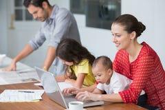 研究有婴孩的膝上型计算机的微笑的母亲,当女儿学习时 免版税库存图片