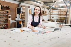 研究木表面上的膝上型计算机的女实业家木匠在建筑工具中 附近智能手机,膝上型计算机,剪贴板 免版税库存图片