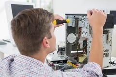 研究残破的计算机的年轻技术员 免版税库存照片