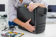 研究残破的计算机的年轻技术员 图库摄影
