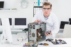 研究残破的计算机的年轻技术员 库存图片