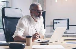 研究流动便携式计算机的成人商人,当坐在木桌上在现代办公室地方时 免版税库存照片