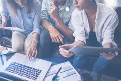研究流动便携式计算机的特写镜头观点的三个年轻工友在办公室 指向的妇女拿着片剂和  免版税库存图片