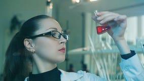 研究烧瓶的妇女在实验室 影视素材