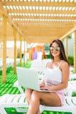 研究甚而假期 太阳镜和帽子的可爱的少妇在躺椅说谎在与膝上型计算机的游泳池附近 库存照片
