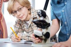 研究生物项目的聪明的年轻学生 免版税库存照片