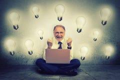 研究电灯泡塞住它的计算机的老人庆祝企业成功 库存图片