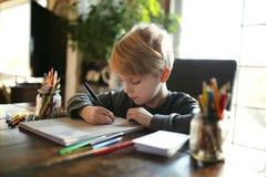研究着色艺术项目的年轻学校年迈的孩子 库存照片