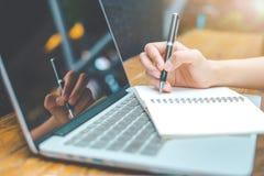 研究笔记本计算机和写在n的妇女` s手 免版税库存照片