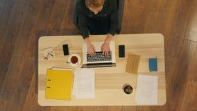 研究线的愉快的偶然企业家键入与膝上型计算机在有一个窗口的办公室在背景中 免版税库存照片