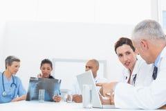 研究膝上型计算机和分析X-射线的医生队  免版税库存照片