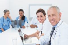 研究膝上型计算机和分析X-射线的医生队  免版税图库摄影