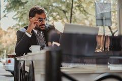 研究膝上型计算机和拿着太阳镜的英俊的商人 图库摄影