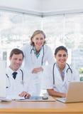 研究膝上型计算机和计算机的微笑的医护人员 免版税库存照片