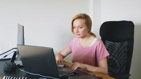 研究膝上型计算机和计算机的美丽的年轻女人,当坐在书桌时 影视素材