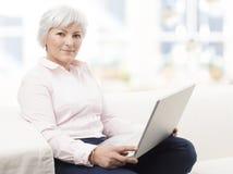 研究膝上型计算机的微笑的资深妇女 免版税库存图片