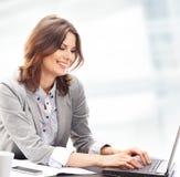 研究膝上型计算机的一名新深色的女实业家 库存照片