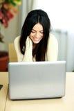 研究膝上型计算机的一名年轻微笑的妇女的画象 库存图片