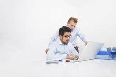 研究膝上型计算机的不同种族的商人在书桌在办公室 库存照片