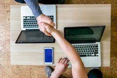 研究膝上型计算机的两青年人在办公室 坐在彼此对面的桌,握手,顶视图,特写镜头上 免版税库存照片