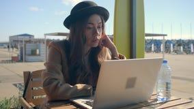 研究膝上型计算机的严肃的女孩坐由咖啡馆 影视素材