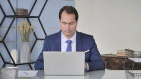 研究膝上型计算机的中间年迈的商人在办公室 股票视频