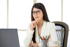 研究膝上型计算机的亚裔微笑的女商人 免版税图库摄影