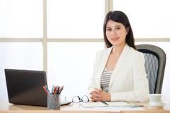 研究膝上型计算机的亚裔微笑的女商人 免版税库存图片