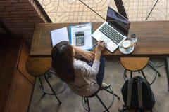 研究膝上型计算机的亚裔自由职业者在咖啡馆 库存图片