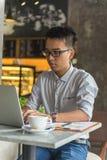 研究膝上型计算机的亚裔自由职业者垂直的照片 库存图片