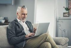 研究膝上型计算机的兴旺的老练的商人 库存照片