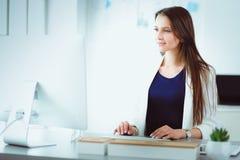 研究膝上型计算机的可爱的女商人在办公室 企业例证JPG人向量 免版税库存图片