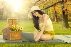 研究膝上型计算机的可爱的妇女在领域 图库摄影