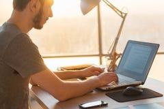 研究膝上型计算机的商人在书桌在办公室 免版税图库摄影