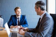 研究膝上型计算机的商人在会议 免版税库存照片