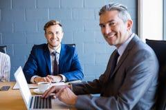 研究膝上型计算机的商人在会议 库存照片