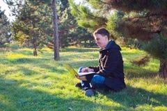 研究膝上型计算机的商人在公园 免版税库存图片