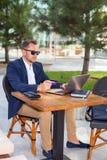 研究膝上型计算机的商人,由信用卡支付 免版税库存图片