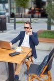 研究膝上型计算机的商人,谈话在手机 库存图片