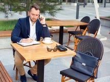 研究膝上型计算机的商人,谈话在手机 免版税库存图片