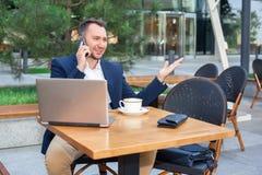 研究膝上型计算机的商人,谈话在手机 库存照片