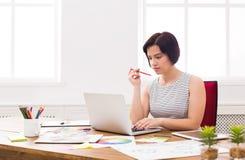 研究膝上型计算机的女商人在办公室 免版税库存照片