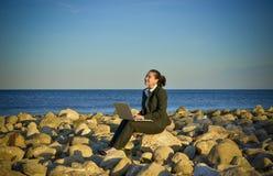 研究膝上型计算机的女商人在海滩 免版税库存图片