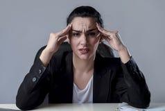 研究膝上型计算机的女商人在遭受强烈的头疼偏头痛的重音的办公室 图库摄影