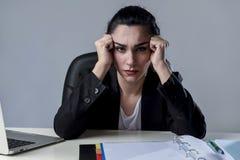研究膝上型计算机的女商人在遭受强烈的头疼偏头痛的重音的办公室 库存照片