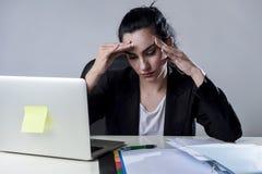 研究膝上型计算机的女商人在遭受强烈的头疼偏头痛的重音的办公室 免版税库存照片