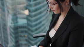 研究膝上型计算机的女商人的特写镜头画象,当由窗口坐一个高地板在办公室时 股票视频